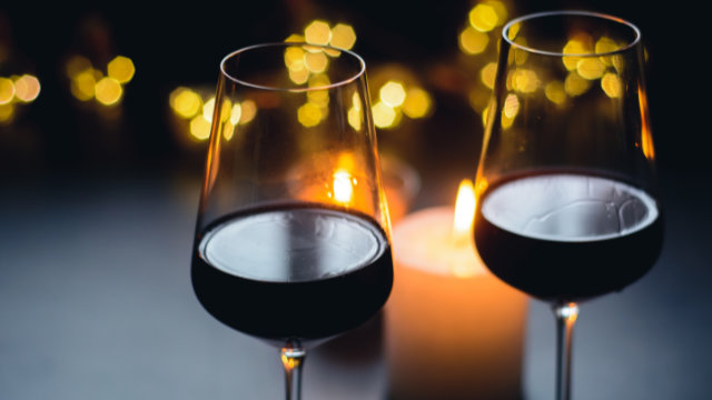 Two wine glasses with red wine in front of candles.