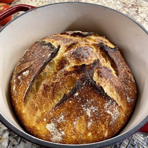 A golden-brown, nicely rounded boule of sourdough in an enameled cast iron dutch oven.