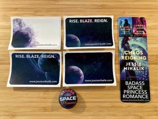Four different book plate stickers with space backgrounds, a bookmark with the PR, AB, and CR covers on it, and a Badass Space Princess button on a bamboo desk background.