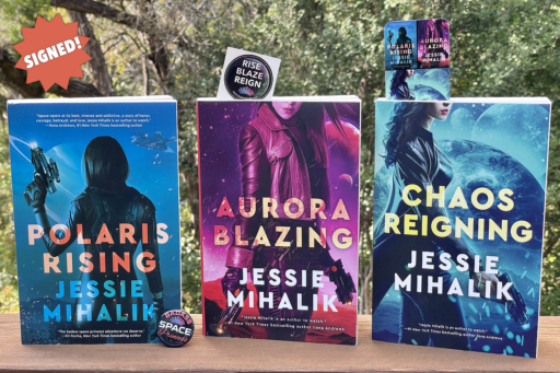 Polaris Rising, Aurora Blazing, and Chaos Reigning standing on my deck railing with greenery in the background. Also includes a bookmark, stickers, and a badass space priciness button.