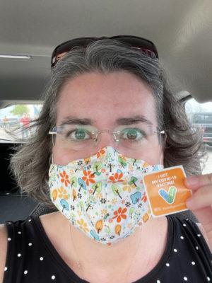 "A selfie of me in the car wearing a mask and holding up a ""I got my covid-19 vaccine!"" sticker."