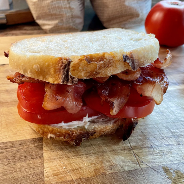A bacon and tomato sandwich on fresh sourdough bread sitting on a wooden cutting board.