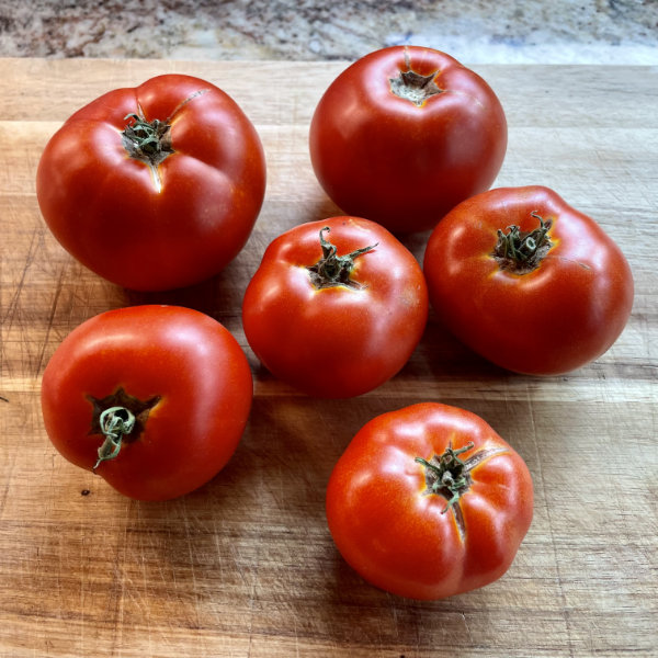 Six beautifully red homegrown tomatoes on a wooden cutting board.