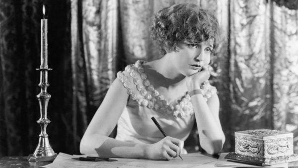 A black-and-white photo of a woman in an evening gown looking sad while writing a letter at a desk with a single candle.