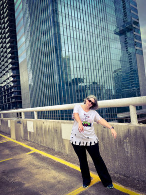 A photo of me in a ripped up t-shirt, pretending to be a zombie on a rooftop parking garage downtown with a tall blue glass building behind me.